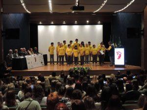 """Alunos da Escola Ecumênica apresentando a música """"Uma Prova de Amor"""" acompanhadas do Professor Paulo Pienta"""